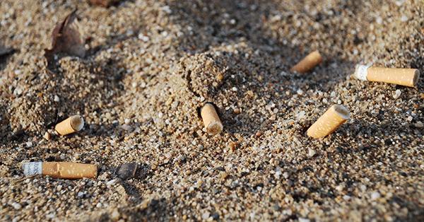 Kippen im Spielplatzsand