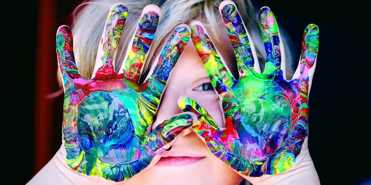 Kind hält bunte Hände vor's Gesicht