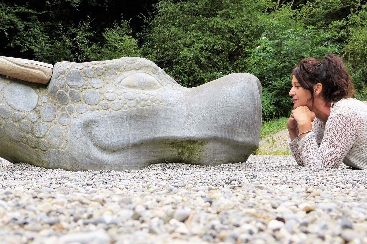 Frau guckt auf Stein-Drachen