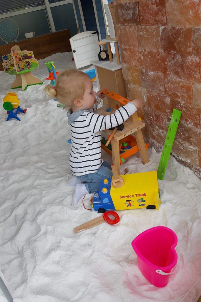 Kleinkind spielt im Salzspielplatz