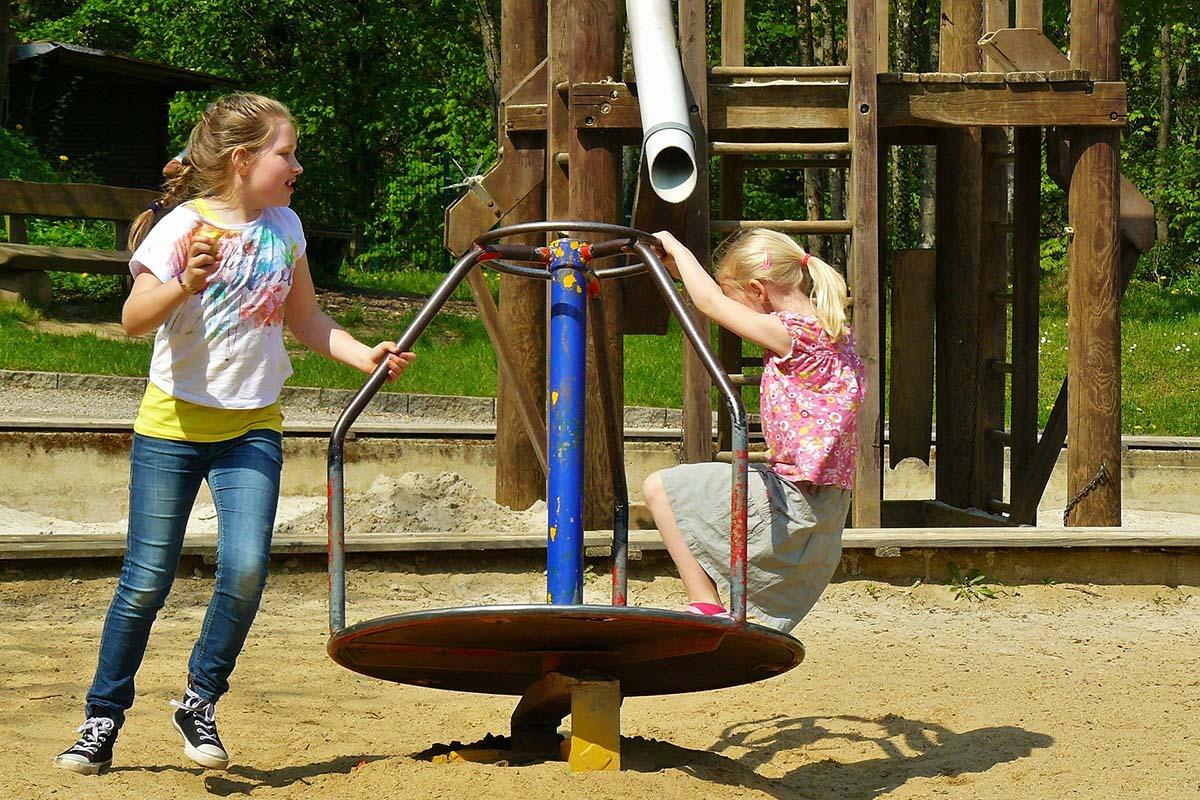 2 Kinder spielen auf dem Spielplatz