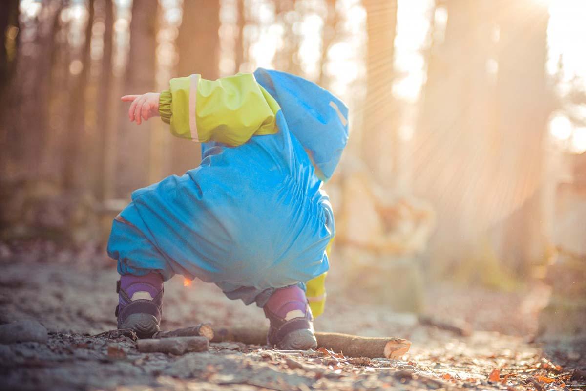Kleinkind mit Matschsachen spielt im Wald