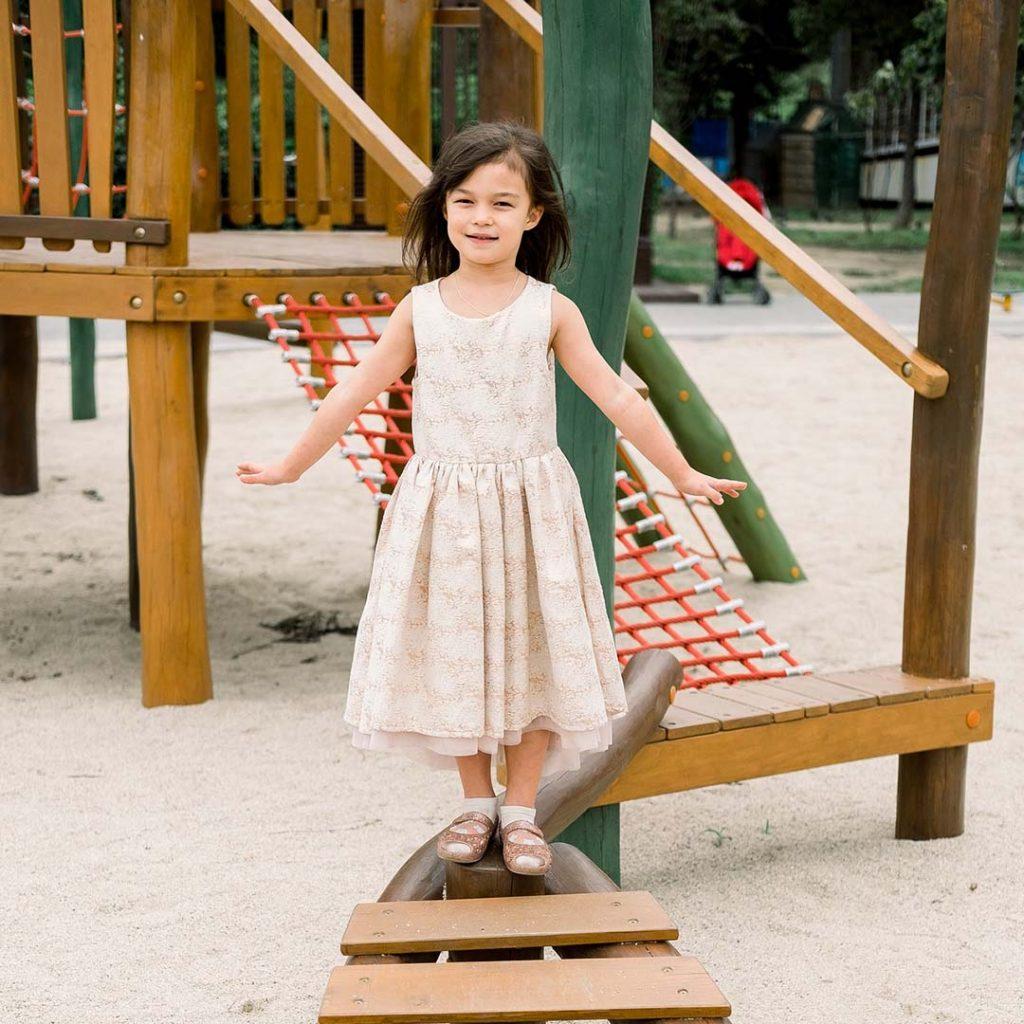 Mädchen im Kleid auf dem Spielplatz