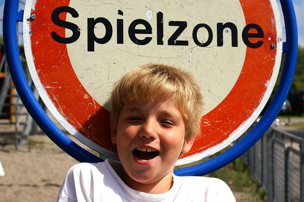 Kind vor einem Verbotsschild Aufschrift Spielzone