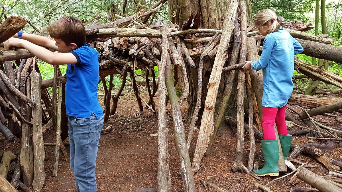 Oudoorkinder bauen mit Ästen im Wald