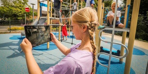 Mädchen ist per App auf einem interaktiven Spielplatz
