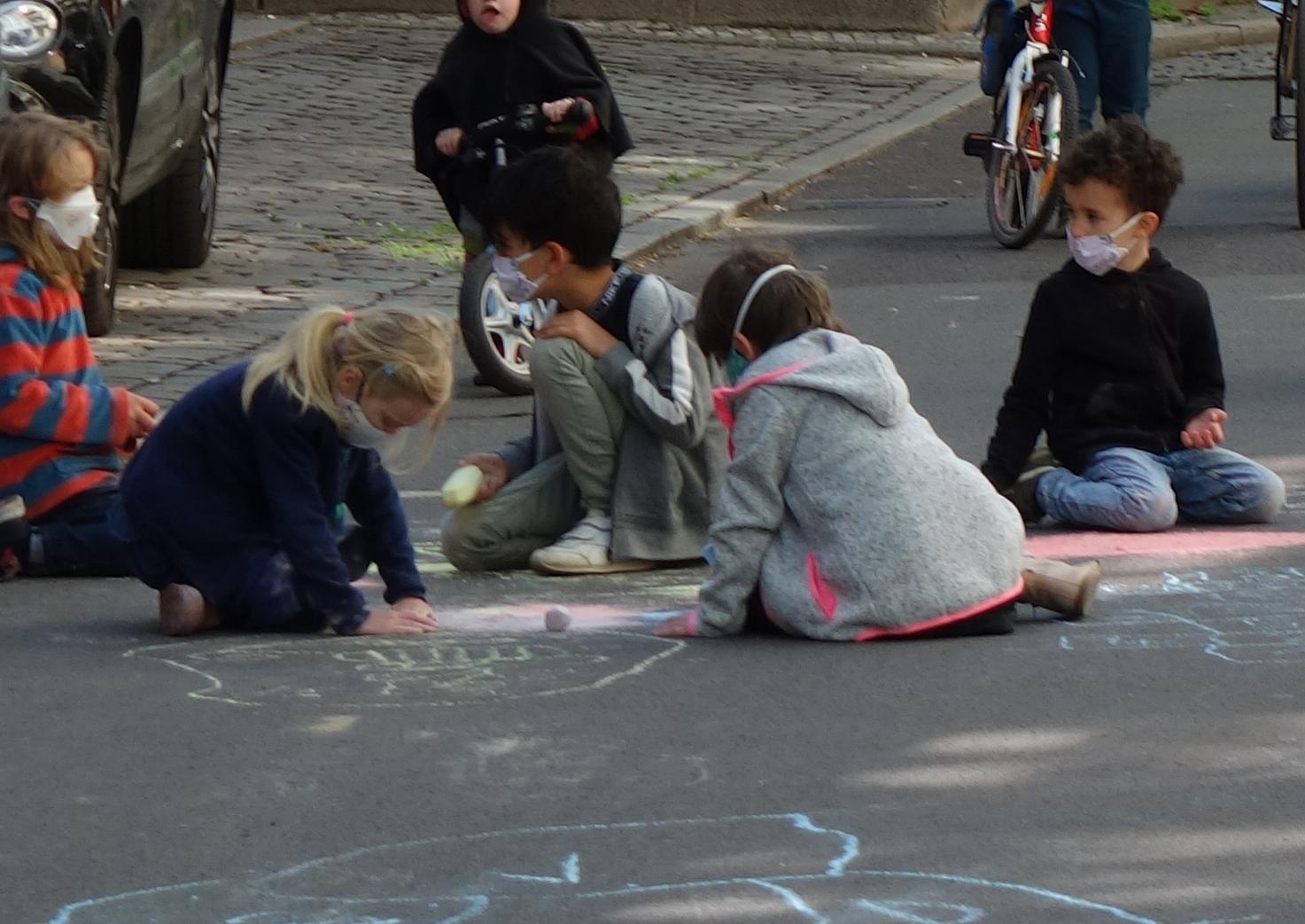Kinder mit Masken malen mit Straßenkreide